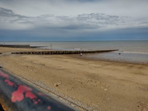 A photograph of the sea, mostly beach. It looks a bit cold and grim.